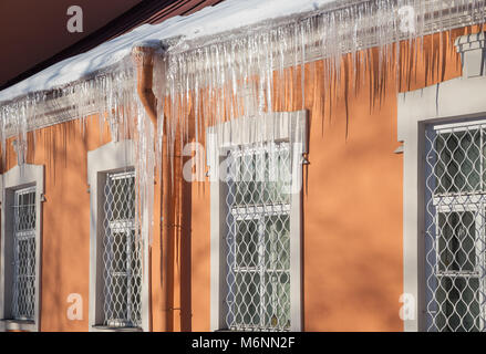 Long icicles hang from the edge of the roof. End of winter - Stock Photo