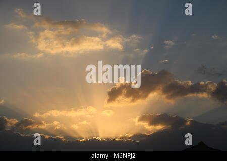 golden rays of early morning sunrise light bursting through clouds - Stock Photo