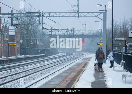 Passengers wait on a platform at an Atherstone train Station covered in snow. The snow has been cleared to make - Stock Photo