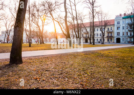 Vilnius, Lithuania - March 17, 2012: Sunset light through the early spring trees in cozy Old Town park on T. Vrublevskio - Stock Photo