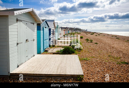 Row of wooden cabins on shingle beach at popular seaside resort Hastings in East Sussex South East England UK - Stock Photo
