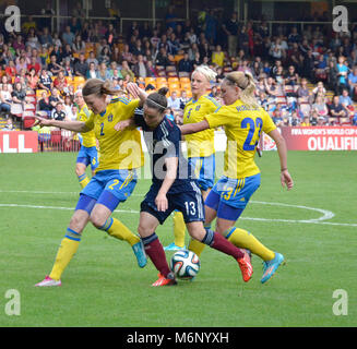 MOTHERWELL, SCOTLAND - JUNE 14th 2014: Scotland's Jane Ross trying to keep the ball from three Swedish players. - Stock Photo