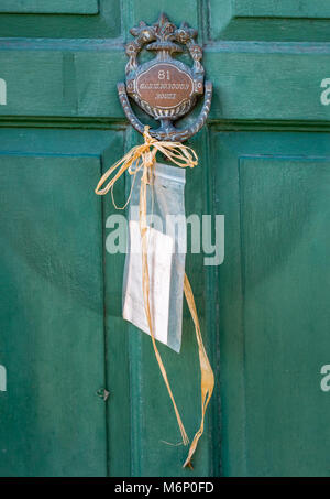 Charming hand written note tied up with raffia to the postman on a door knocker in a small town in central England - Stock Photo