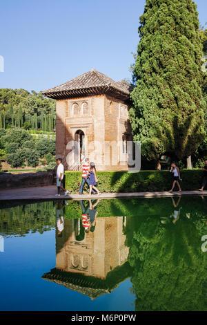 Granada, Andalusia, Spain - July 18th, 2010 : Tourists walk past the Partal chapel (Oratorio del Partal) reflected - Stock Photo