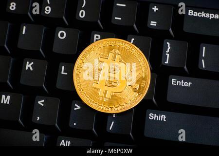 Golden Bitcoin virtual money on black keyboard. Close-up. - Stock Photo
