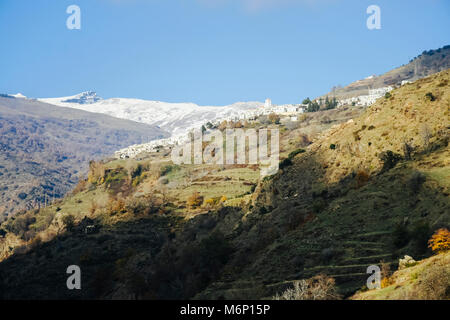 View of whitewashed Capileira village with snow-capped Sierra Nevada peaks in background in  Las Alpujarras, Granada - Stock Photo