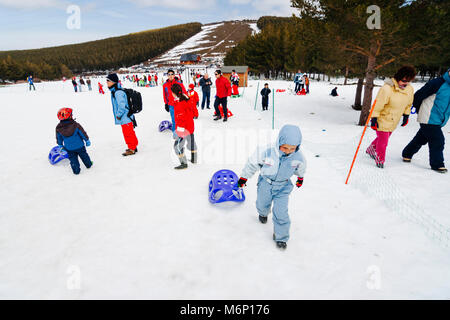 A child in ski suit is pushing a sledge on a snow-covered field at Puerto de la Ragua Ski resort in Sierra Nevada, - Stock Photo