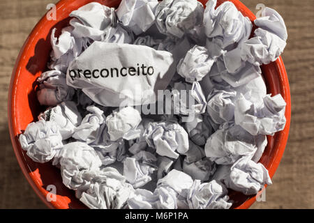 Crumpled paper written preconceito, portuguese word for prejudice, inside the trash can. Paper balls. Old and abandoned - Stock Photo