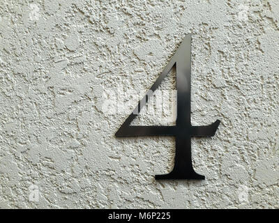 Made of chromed metal figure four, reinforced on the wall beige. - Stock Photo