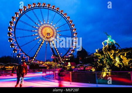 Neptunbrunnen, ferris wheel and ice skater at a Winter market in  Berlin, Germany - Stock Photo