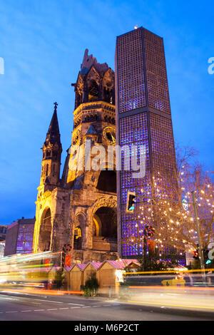 Kaiser Wilhelm Memorial Church illuminated at dusk in Breitscheidplatz, Charlottenburg district, Berlin, Germany - Stock Photo