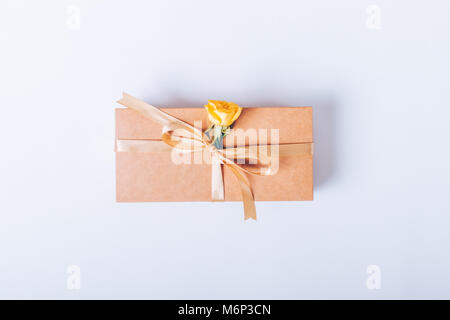 Gift box with beige ribbon and yellow flower on white table top view - Stock Photo