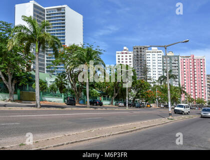 Street view of Maputo, the capital of Mozambique with a road in front of the buildings - Stock Photo