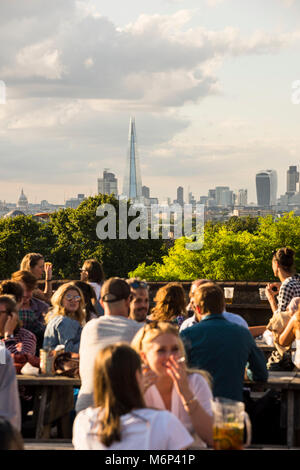 People socialising and enjoying a drink together at outdoor rooftop bar with view of the city. - Stock Photo