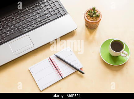 High-angle shot of a home office desk space with laptop, cactus plant, coffee cup and saucer and a calendar with - Stock Photo
