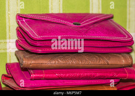 Close up detail of a stack of colourful handmade leather purses for sale in the souk artisan in Fes, Morocco. - Stock Photo
