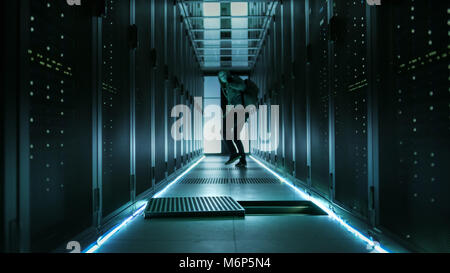 Shot of a Masked Hacker in a Hoodie Running Away and Watching Back with Laptop in a Corporate Data Center. - Stock Photo