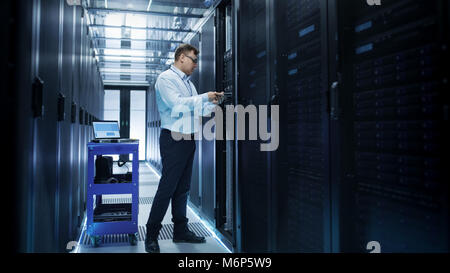 IT Engineer Installing Hard Drives into Working Rack Server. He's Working in Data Center. - Stock Photo