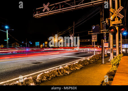 Traffic passing railroad crossing tracks on a busy road during rush hour. Flashing lights and gate stop cars when - Stock Photo