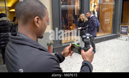 New York City - Circa 2017: Man walks down NYC Manhattan sidewalk using DJI Osmo 4K stabilizer camera recording - Stock Photo