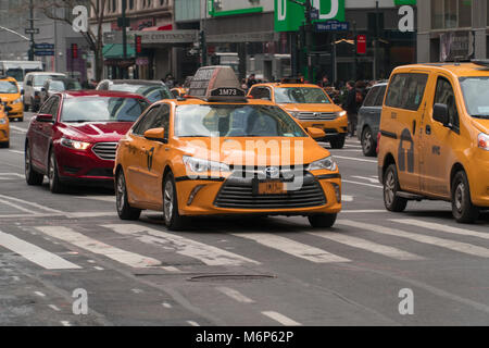 New York City - Circa 2017: Yellow taxi cab driving in streets of Manhattan on a busy day. Taking passengers to - Stock Photo