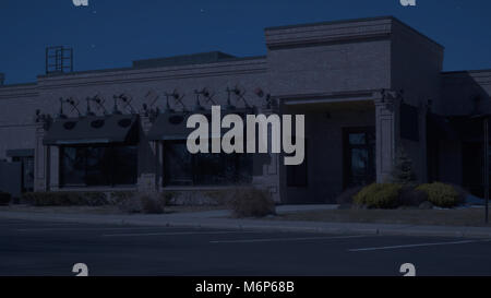 Exterior generic restaurant diner establishing photo night time. Tight shot of front entrance with no signage for - Stock Photo