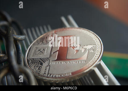 Silver litecoin coin  lying on the  aluminum computer cooler next to a copper chain. Cryptocurrency digging difficulty, - Stock Photo