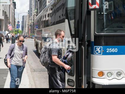 New York City, Circa 2017: People enter Manhattan MTA public transportation bus on 5th avenue. Local riders conserve - Stock Photo