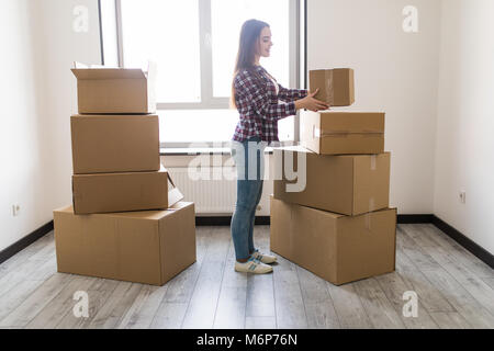 Woman packing and unpacking belongings in a carton box when moving home. - Stock Photo