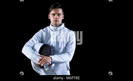 Portrait Shot of a Young Fencer Standing and Looking into Camera. Shot Isolated on Black Background. - Stock Photo