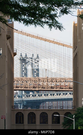 Manhattan and Brooklyn bridges vertically framed view between two New York City apartment buildings during the day