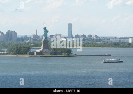 Statue of Liberty wide aerial photo over New York Harbor water on summer day July 4th independence day weekend - Stock Photo