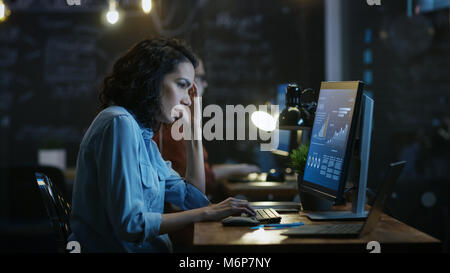 Stressed, Overworked Female Financier Holds Her Head in Hands while Working on a Personal Computer. In the Background - Stock Photo