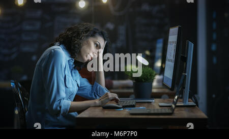 Tired, Overworked Female Financier Holds Her Head in Hands while Working on a Personal Computer. In the Background - Stock Photo