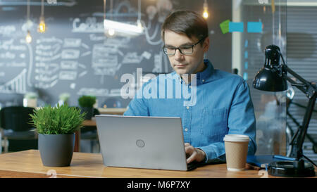 Handsome Young Office Employee Works on a Laptop Computer. He's Working in the Creative Stylish Office. - Stock Photo