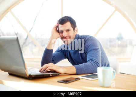 Portrait of young man with his forehead rested on his hand and looking at camera while sitting at desk and working - Stock Photo