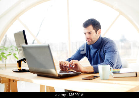 Portrait of young casual businessman using laptop while working at the office. - Stock Photo