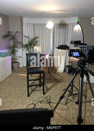 A small room setup for an interview style video shoot behind the scenes. Motion picture camera, lighting, reflector - Stock Photo