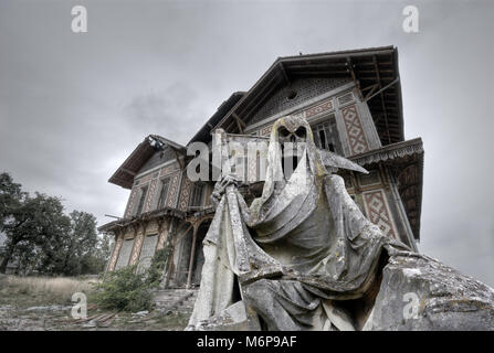 haunted house with a gream reaper statue in foreground - Stock Photo