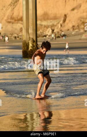 Young African-American man on a skim board, skimming, at beach during sunset, gliding across waves, San Diego, California, - Stock Photo