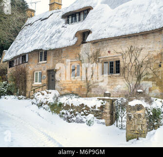 Stanton stone thatched cottage in the winter snow. Stanton, Cotswolds, Worchestershire, England - Stock Photo