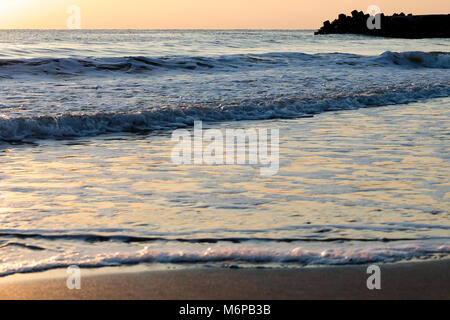 Brightly lit seascape background with golden colored gentle breaking sea waves lapping on the beach at sunrise - Stock Photo
