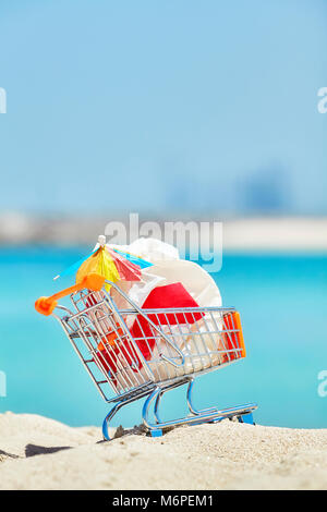 Miniature shopping cart with plastic garbage left by tourist on a tropical beach, environmental pollution concept - Stock Photo