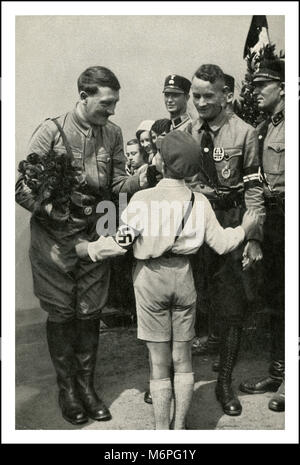 Pre WW2 1930's Adolf Hitler holding flowers with NSDAP henchmen greeting young boy party member who is wearing a - Stock Photo