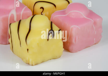 Frency Fancies fondand cakes on a white backfround - Stock Photo