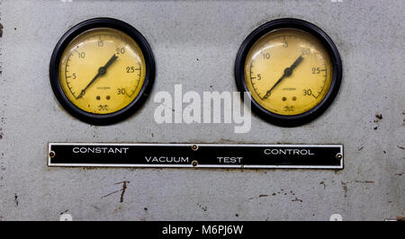 Vintage antique automotive machine shop vacuum gauges on a silver sheet metal plate with sign - Stock Photo