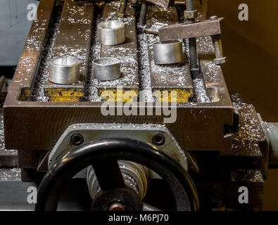 Vintage antique automotive machine shop milling table with aluminum machined components and filings with an adjustment - Stock Photo