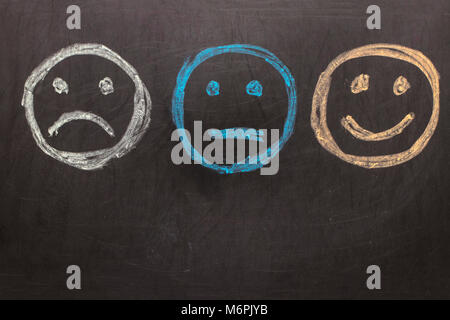 Drawing Unhappy and Happy Smileys on Blackboard Background - Stock Photo
