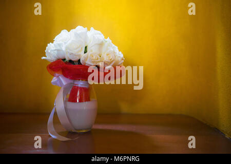 The bouquet of the bride with cream roses and the bride's shoes, on the wooden floor wth yellow background, the - Stock Photo