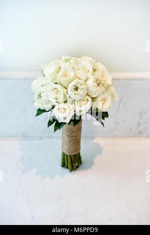 Bride's bouquet made with white cream roses on the white wall - Stock Photo